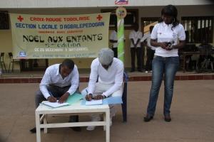 Tässä allekirjoitetaan yhteistyösopimusta Punaisen Ristin Agbalepedoganin paikallisjärjestön ja Toivon Solmu  ry:n välillä. Allekirjoittajina puheenjohtajat Akuete Kpakpo ja Aklaesso Tontasse